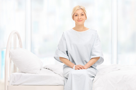 Photo for Blond female patient posing seated on a hospital bed and looking at the camera - Royalty Free Image