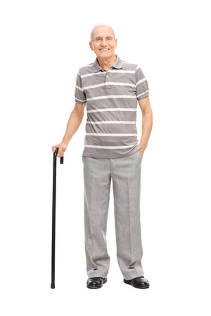 Photo for Full length portrait of an old man in a casual polo shirt holding a cane and posing isolated on white background - Royalty Free Image