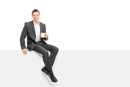 Photo pour Young businessman in a gray suit holding a cup of coffee and sitting on a blank panel isolated on white background - image libre de droit