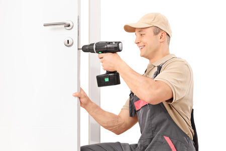 Foto de Young male locksmith screwing a screw on a lock of a door with a hand drill isolated on white background - Imagen libre de derechos