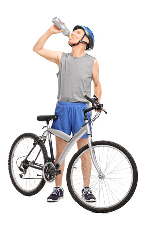 Foto de Full length portrait of a senior biker standing behind his bicycle and drinking water isolated on white background - Imagen libre de derechos
