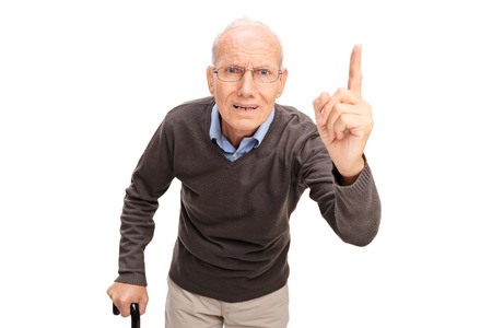 Photo pour Angry senior man with a cane scolding and gesturing with his finger isolated on white background - image libre de droit