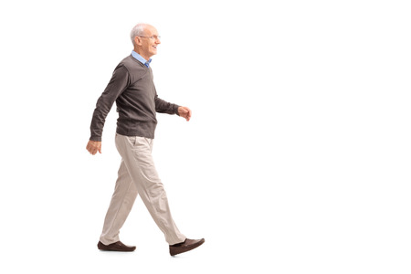 Photo pour Full length profile shot of a casual senior man walking and smiling isolated on white background - image libre de droit