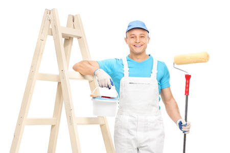 Photo for Young male house painter in a white clean jumpsuit holding a paint roller and leaning on a wooden ladder isolated on white background - Royalty Free Image