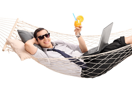 Photo pour Young businessman lying in a hammock with a laptop in his lap and drinking an orange cocktail isolated on white background - image libre de droit