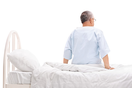 Rear view studio shot of a senior patient in a hospital gown sitting on a hospital bed isolated on white background