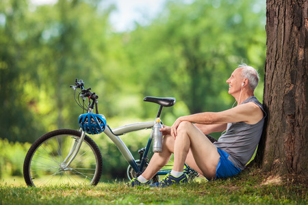 Photo pour Active senior man listening to music on headphones seated by a tree in a park - image libre de droit