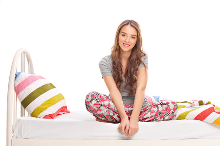 Beautiful brunette woman sitting on a bed in her pajamas and looking at the camera isolated on white background