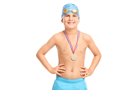 Junior swimming champion with blue swim cap and swim trunks looking at the camera isolated on white background