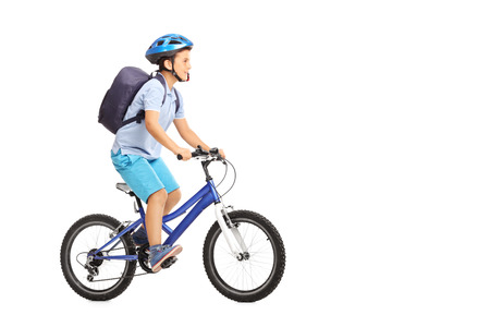 Foto de Studio shot of a schoolboy with a helmet and a blue backpack riding a bike isolated on white background - Imagen libre de derechos