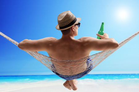 Foto de Relaxed young guy lying in a hammock and drinking beer on a sunny beach by the ocean - Imagen libre de derechos