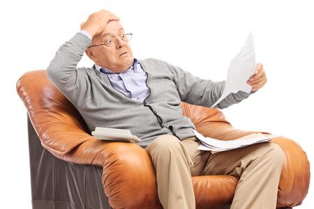 Foto de Shocked senior gentleman looking at his bills in disbelief seated in an armchair isolated on white background - Imagen libre de derechos