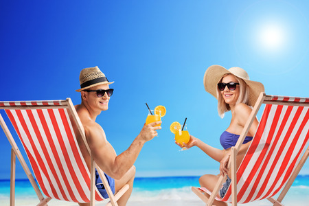 Foto de Young man and woman sitting on sun loungers and holding cocktails at a sunny beach - Imagen libre de derechos
