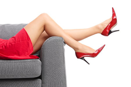 Close-up on a female legs with red high heels lying on a gray sofa isolated on white background