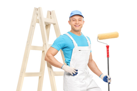 Photo for Male house painter in a clean white overalls holding a paint roller and leaning on a ladder isolated on white background - Royalty Free Image