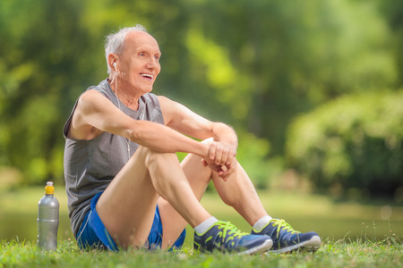 Photo pour Athletic senior in sportswear sitting on grass in a park and listening to music on headphones - image libre de droit