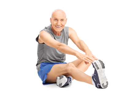 Photo for Studio shot of a senior in sportswear stretching his leg seated on the floor isolated on white background - Royalty Free Image