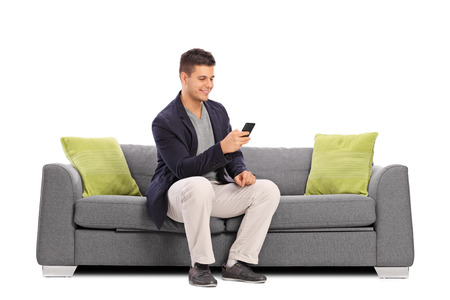 Photo pour Cheerful young man sitting on a gray sofa and typing on his cell phone isolated on white background - image libre de droit