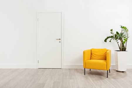 Photo pour Contemporary waiting room with a yellow armchair and a plant in a white flowerpot behind it - image libre de droit