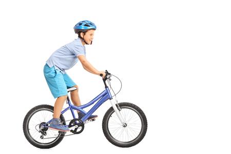 Foto de Profile shot of a little boy with blue helmet riding a small blue bike isolated on white background - Imagen libre de derechos