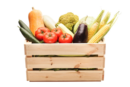Studio shot of a wooden crate full of fresh vegetables isolated on white background