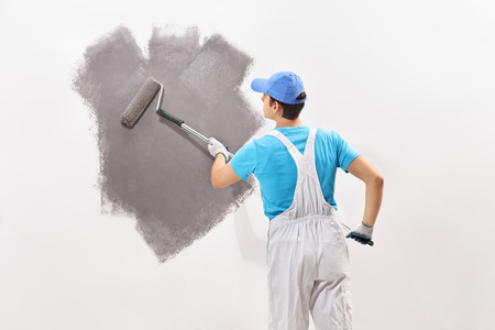 Photo for Rear view shot of a young male decorator in white overalls painting a wall with gray color - Royalty Free Image