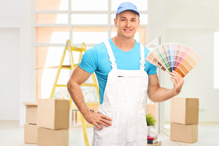 Photo for Young male house painter in a white jumpsuit holding a color swatch in an apartment and looking at the camera - Royalty Free Image