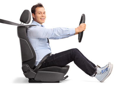 Photo for Profile shot of a young man driving seated on car seat and looking at the camera isolated on white background - Royalty Free Image