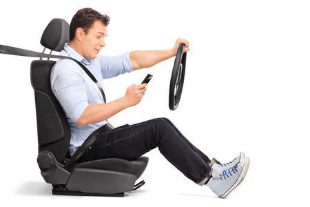 Foto de Studio shot of a young man driving a car and looking at his cell phone isolated on white background - Imagen libre de derechos