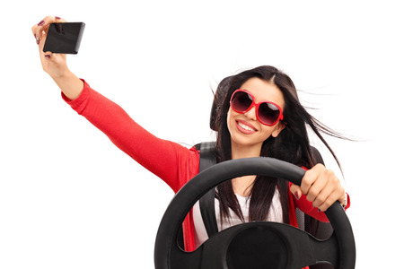 Photo for Young cheerful woman taking a selfie while driving a car isolated on white background - Royalty Free Image