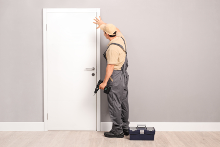 Photo pour Young handyman installing a white door with an electric hand drill in a room - image libre de droit