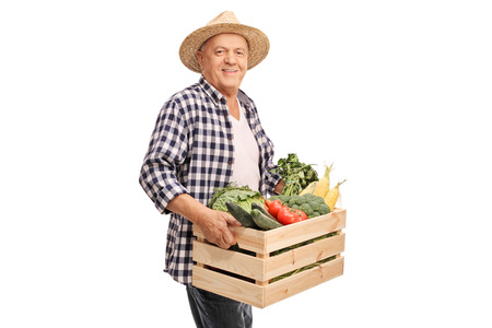 Cheerful mature farmer holding a crate full of fresh vegetables and looking at the camera isolated on white background