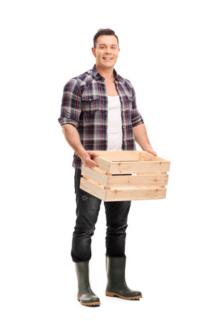 Full length portrait of a young male farmer holding an empty wooden crate and looking at the camera isolated on white background