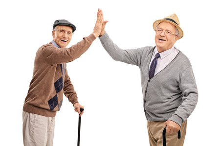 Foto de Two cheerful senior gentlemen high-five each other and looking at the camera isolated on white background - Imagen libre de derechos
