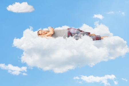 Photo pour Tranquil scene of a young woman dreaming and sleeping on a cloud up in the sky - image libre de droit