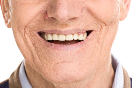 Foto de Close-up on cheerful senior man smiling isolated on white background - Imagen libre de derechos