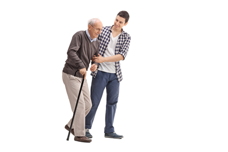 Foto de Young man helping a senior gentleman with a cane isolated on white background - Imagen libre de derechos