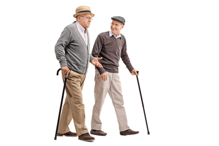 Photo pour Two senior gentlemen walking and talking to each other isolated on white background - image libre de droit