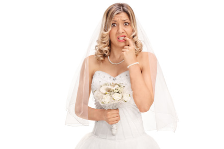 Foto de Nervous young bride biting her nails and looking at the camera isolated on white background - Imagen libre de derechos