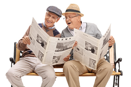Photo pour Senior showing something in the newspaper to his friend seated on a bench isolated on white background - image libre de droit