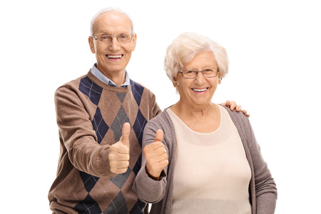 Photo pour Senior man and woman giving thumbs up and looking at the camera isolated on white background - image libre de droit