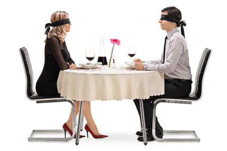 Photo pour Young man and woman on a blind date seated at a restaurant table isolated on white background - image libre de droit