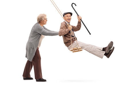 Foto de Elderly woman pushing a man on a wooden swing isolated on white background - Imagen libre de derechos