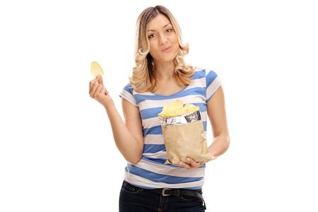 Joyful young woman eating potato chips isolated on white background