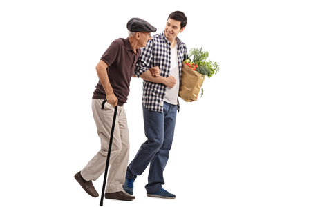 Foto de Kind young man helping a senior gentleman with his groceries isolated on white background - Imagen libre de derechos
