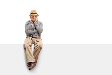 Foto de Depressed senior man sitting on a blank panel and contemplating isolated on white background - Imagen libre de derechos