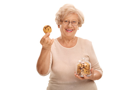 Photo pour Happy mature woman holding a cookie and a jar full of cookies isolated on white background - image libre de droit