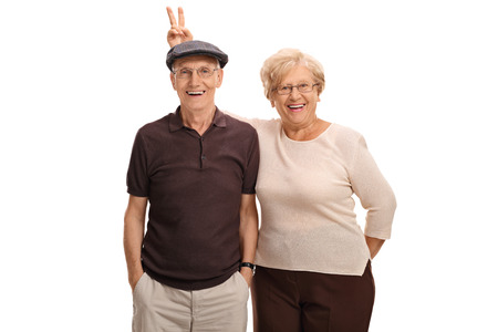 Photo for Elderly woman pranking her husband with bunny ears isolated on white background - Royalty Free Image