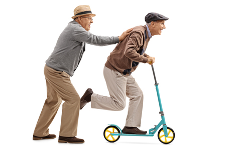 Foto de Full length profile shot of a mature man pushing another man on a scooter isolated on white background - Imagen libre de derechos