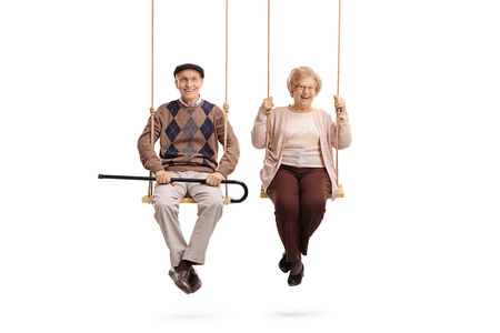 Photo pour Elderly man and an elderly woman sitting on swings isolated on white background - image libre de droit